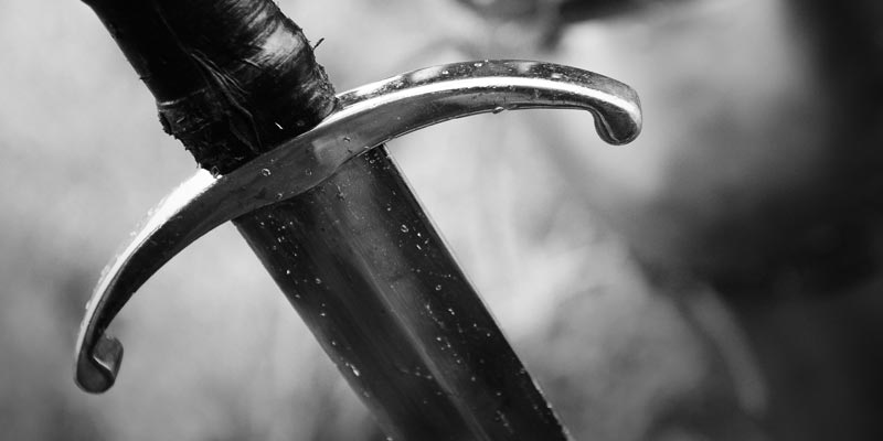 A black and white image of a sword thrust into the ground