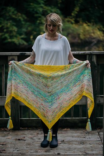 A woman holding a shawl of blended green and  yellow hues