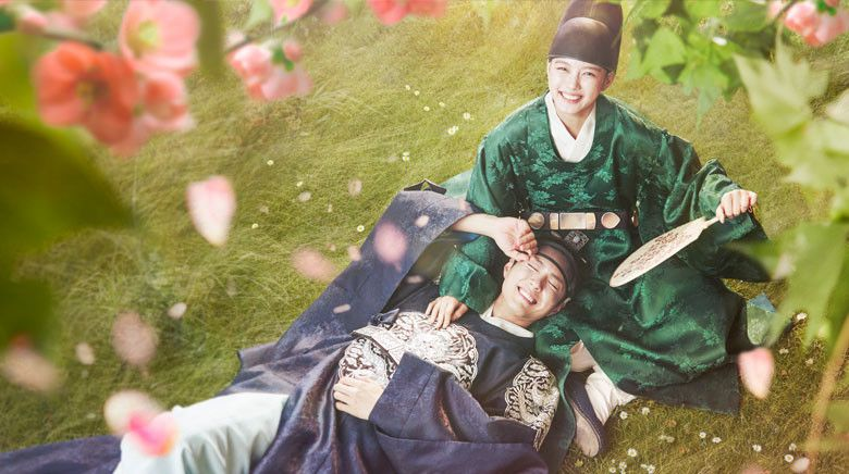 Prince and a girl in a eunuch outfit under flowering trees laughing.