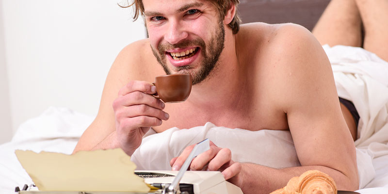 Half naked writer dude in bed typing on a parchment in an ancient typewriter and drinking cofee