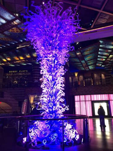 Dale Chihuly sculpture, tall, backlit.